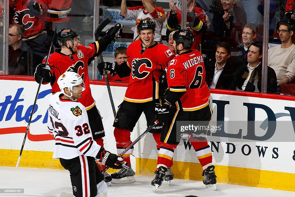 Lance Bouma #17, Matt Stajan #18 and Dennis Wideman #6 of the Calgary Flames celebrate a goal against the Chicago Blackhawks at Scotiabank Saddledome on January 28, 2014 in Calgary, Alberta, Canada.