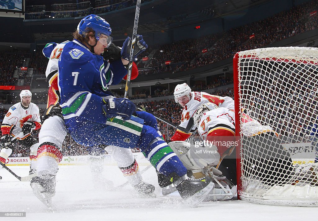Lance Bouma #17 of the Calgary Flames checks David Booth #7 of the Vancouver Canucks in front of Karri Ramo #31 of the Flames during their NHL game at Rogers Arena April 13, 2014 in Vancouver, British Columbia, Canada. Vancouver won 5-1.