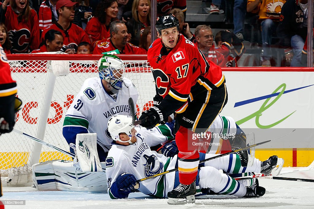 Lance Bouma #17 of the Calgary Flames checks Henrik Sedin #33 of the Vancouver Canucks at Scotiabank Saddledome on October 6, 2013 in Calgary, Alberta, Canada.
