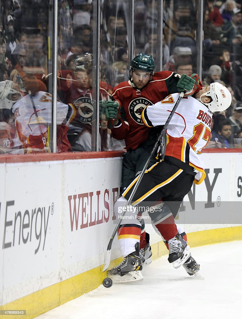 Lance Bouma #17 of the Calgary Flames checks Nate Prosser #39 of the Minnesota Wild into the boards during the first period of the game on March 3, 2014 at Xcel Energy Center in St Paul, Minnesota.