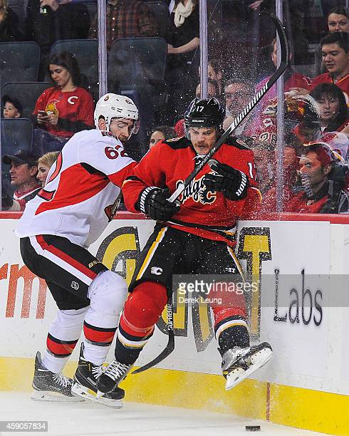 Lance Bouma of the Calgary Flames gets checked into the boards by Eric Gryba of the Ottawa Senators during an NHL game at Scotiabank Saddledome on...