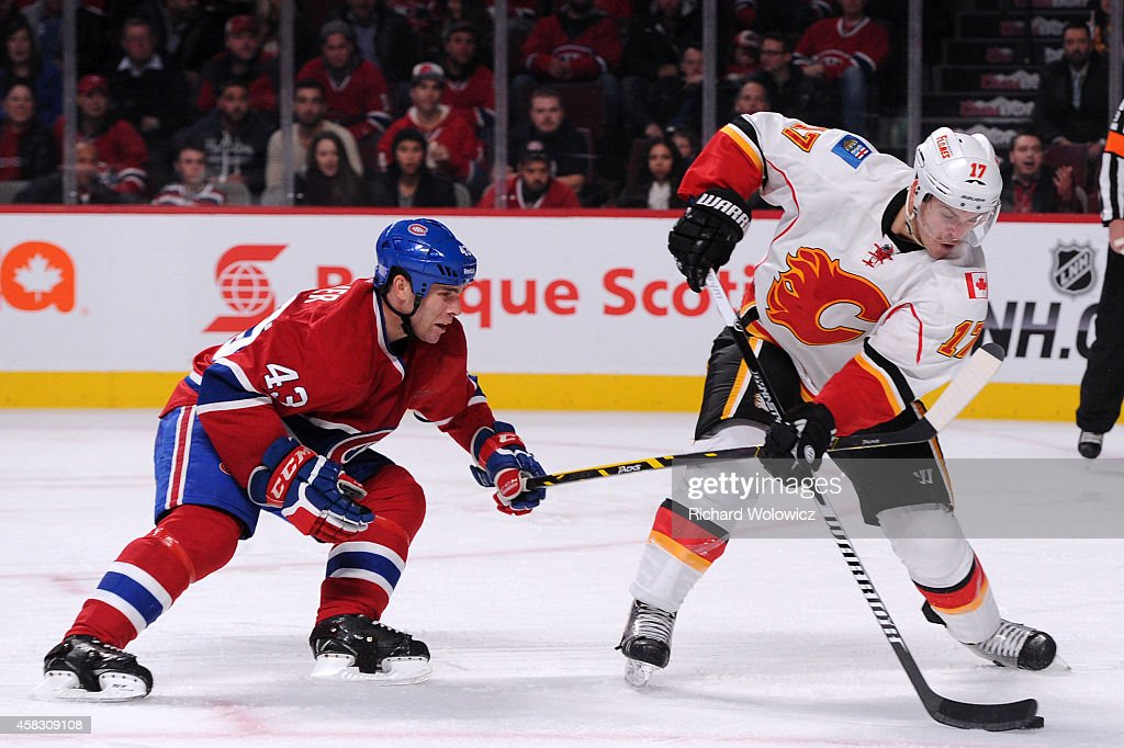 Lance Bouma of the Calgary Flames skates with the puck while being defended by Mike Weaver of the Montreal Canadiens during the NHL game at the Bell...