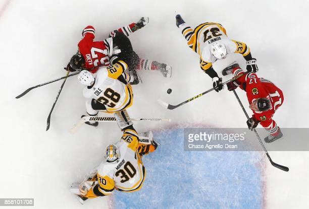 Lance Bouma of the Chicago Blackhawks amd Carter Rowney of the Pittsburgh Penguins battle for the puck at the United Center on October 5 2017 in...