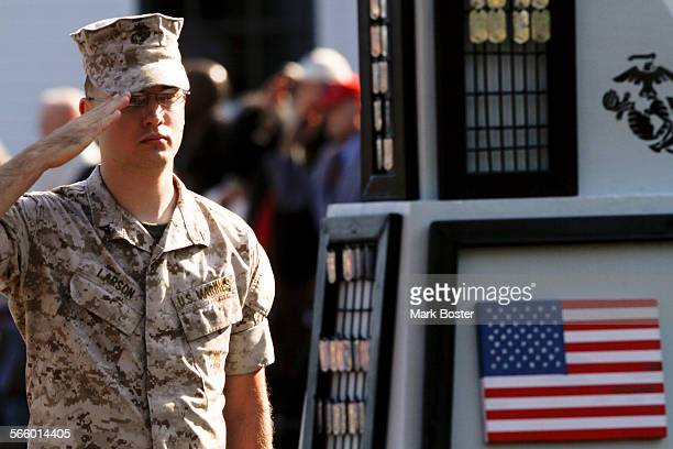 Lance Corp Jacob Larson salutes his fallen brothers after placing additional dogtags on the memorial for the 125 Marines and sailors killed in...