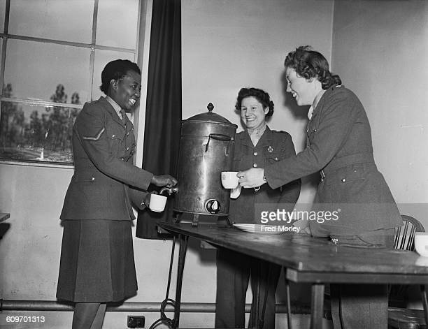 Lance Corporal Adina Williams of the British Auxiliary Territorial Service pours a cup of tea from an urn in the canteen at her barracks UK 26th...