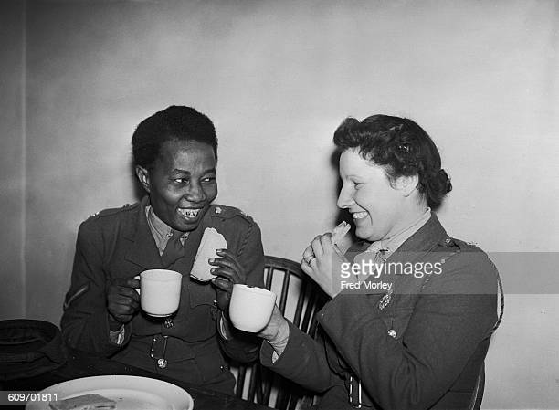 Lance Corporal Adina Williams of the British Auxiliary Territorial Service has a cup of tea and a sandwich with another member of her unit UK 26th...