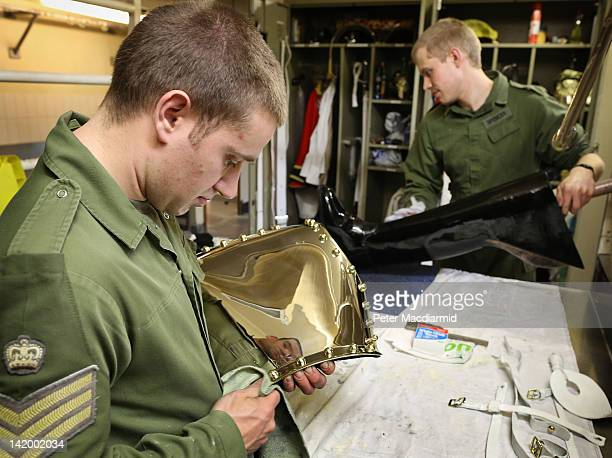 Lance Corporal of Horse Jeffrey Brown polishes his ceremonial breast plate known as a Cuirass as his colleague Trooper Edward Spencer polishes one of...