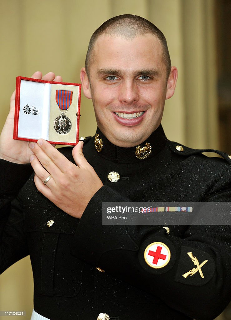 Lance Corporal Ryan Shelley of the Royal Marines holds his George Medal, after it was presented to him by the Prince of Wales, at the Investiture Ceremony on June 23, 2011 at Buckingham Palace, London.