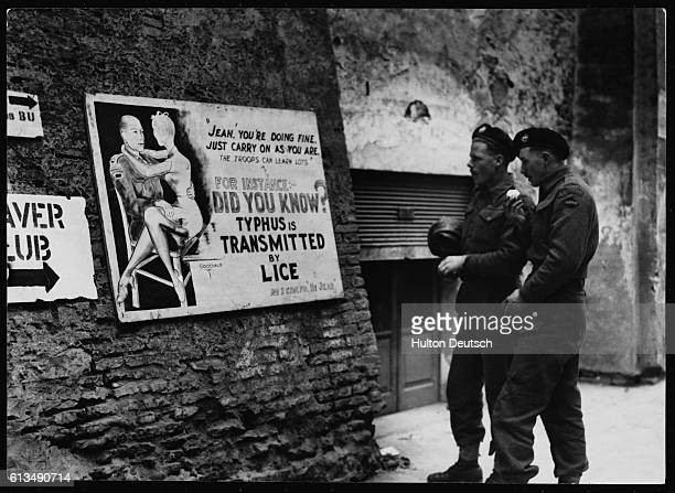 Lance Corporal Tom Gargetty and Trooper Gordon Roddie read a poster warning of the danger of catching typhus from lice