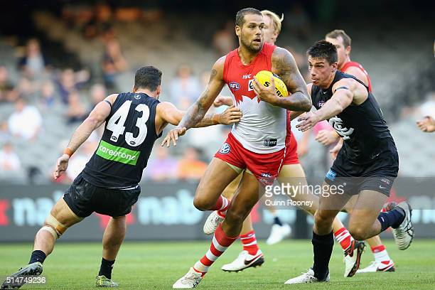 Lance Franklin of the Swans breaks through a tackle by Simon White of the Blues during the NAB Challenge AFL match between the Carlton Blues and the...