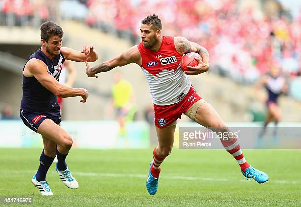 Lance Franklin of the Swans fends off Alex Silvagni of the Dockers during the First Qualifying Final AFL match between the Sydney Swans and the...