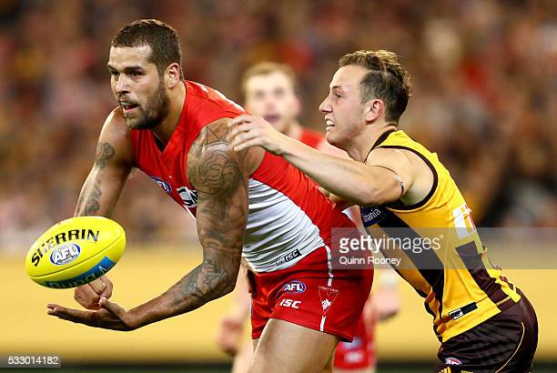 Lance Franklin of the Swans handballs whilst being tackled by Billy Hartung of the Hawks during the round nine AFL match between the Hawthorn Hawks...