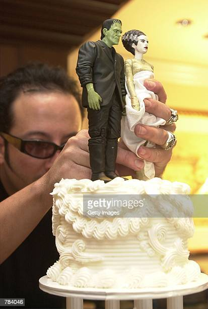 Lance Huston puts a Frankenstein and bride figure on top of a huge wedding cake part of a mass wedding February 14 2001 at Universal Studios in...