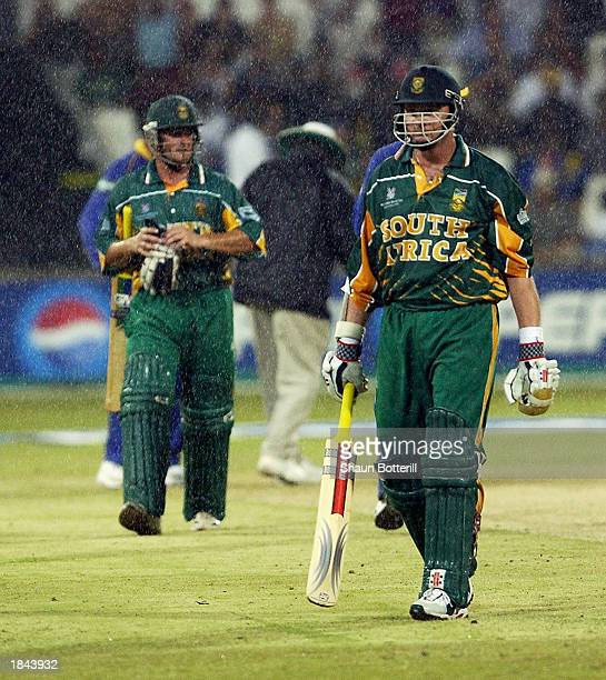 Lance Klusener and teammate Mark Boucher of South Africa leave the field as rain falls during the ICC Cricket World Cup 2003 Pool B match between...