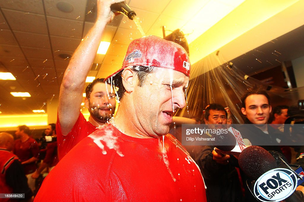 Lance Lynn #31 pours champagne on manager Mike Matheny #22 of the St. Louis Cardinals in the locker room as they celebrate their 6 to 1 win over the Pittsburgh Pirates during Game Five of the National League Division Series at Busch Stadium on October 9, 2013 in St Louis, Missouri.