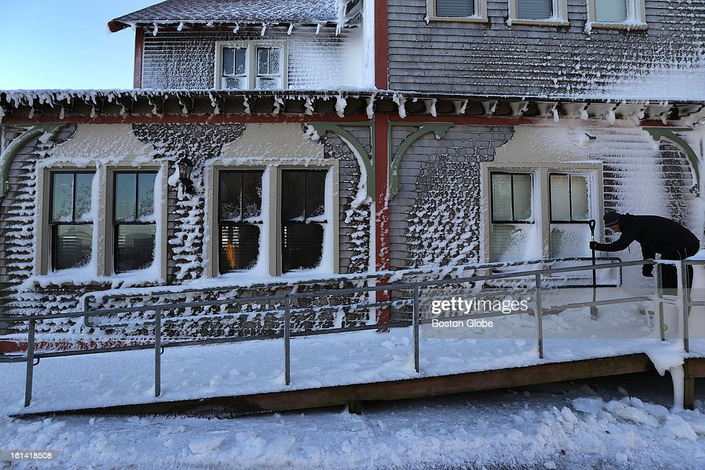Lance Marquardt, of Duxbury, chips ice off a loading ramp outside the Fairview Restaurant and Inn on Ocean Street in Marshfield on Sunday, Feb. 10, 2013, after a blizzard hit New England.
