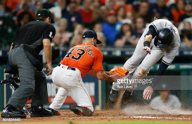 Lance McCullers Jr #43 of the Houston Astros tags out Austin Romine of the New York Yankees as he atempts to score on a wild pitch in the fourth...