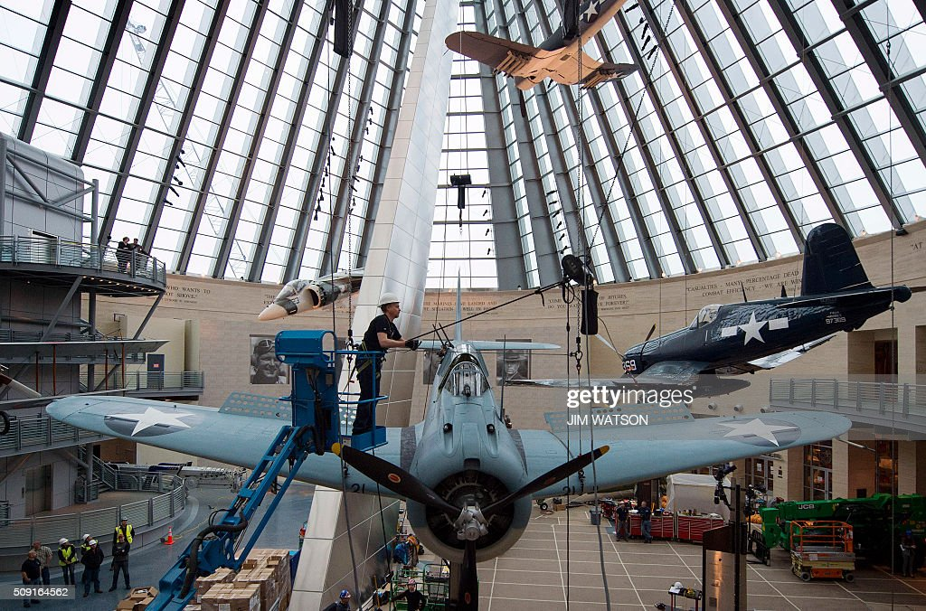 Lance Retallick, a technician with Weiss Theatrical Solutions secures a safety line as a World War II SBD Dauntless dive bomber is craned into position at the National Museum of the Marine Corps in Triangle, Virginia, February 9, 2016. The aircraft transferred from the Marine Corps to the US Navy Carrier Qualification Training Unit in Glenview, Illinois in 1943. It was lost in a training accident that same year when the plane crashed and sank to the bottom of Lake Michigan. A team from the National Museum of Naval Aviation recovered the plane in 1991, 48 years after it crashed. / AFP / JIM WATSON