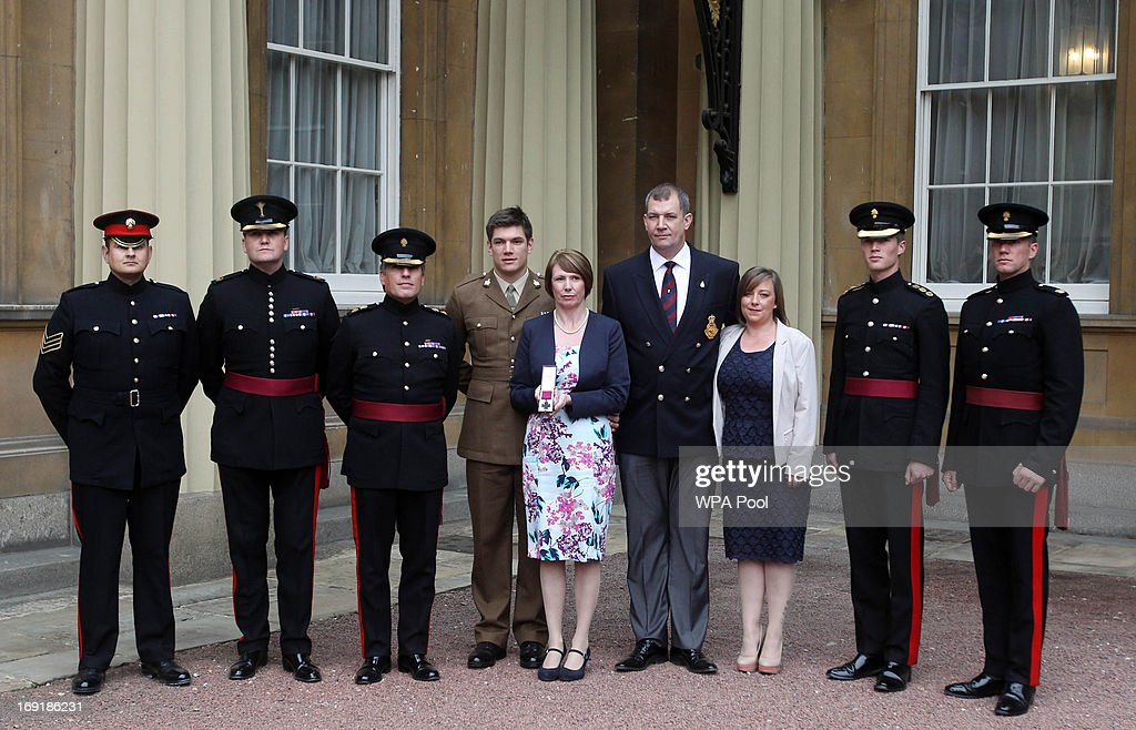 Lance Sergeant Strydom, Major Chris Sargent, Lieutenant Colonel Bowder, Coran Ashworth with parents Mrs Kerry Ashworth and Duane Ashworth who received the Victoria Cross conferred on their late son (Lance Corporal James Ashworth), Caroline (Duane's new partner) Corporal Dobbin and Major Ashfield pose outside Buckingham Palace on May 21, 2013 in London, England.