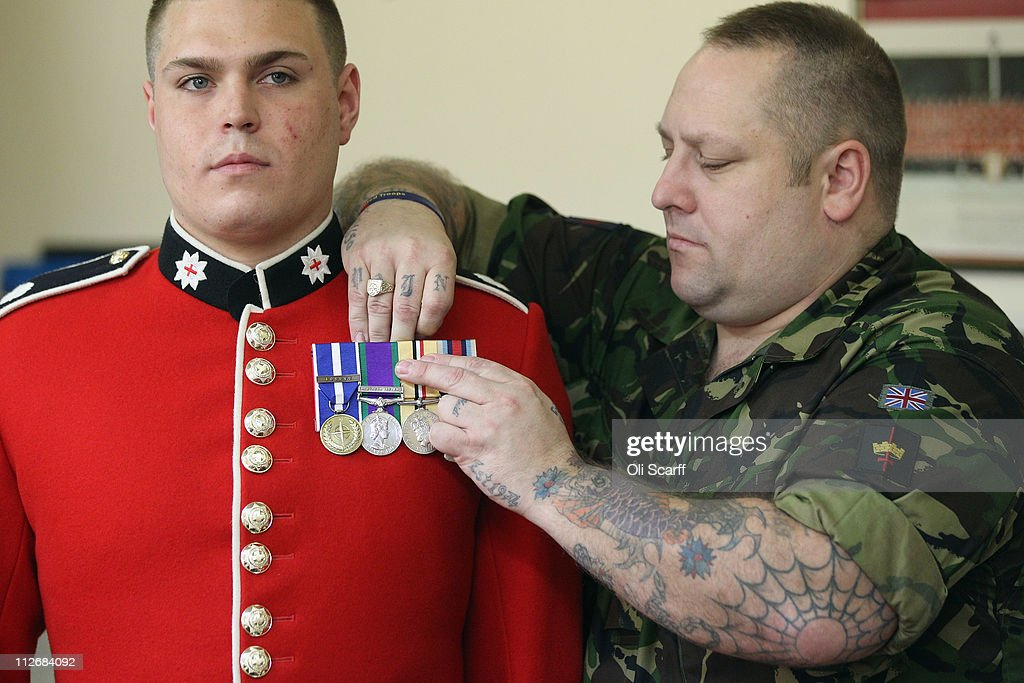 Lance Sergent Martin Mitchell (R) pins medals to Coldstream Guardsman Martin Hughes in the Tailor Shop in Wellington Barracks on April 20, 2011 in London, England. Soldiers involved in the Royal Wedding of Prince William and Catherine Middleton are preparing their ceremonial duties ahead of the day.