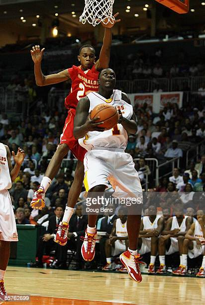 Lance Stephenson of the East Team drives under John Henson of the West Team in the 2009 McDonald's All American Men's High School Basketball Game at...