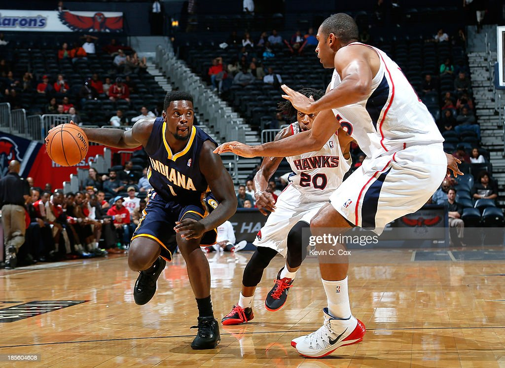 Lance Stephenson #1 of the Indiana Pacers drives against Cartier Martin #20 and Al Horford #15 of the Atlanta Hawks at Philips Arena on October 22, 2013 in Atlanta, Georgia.