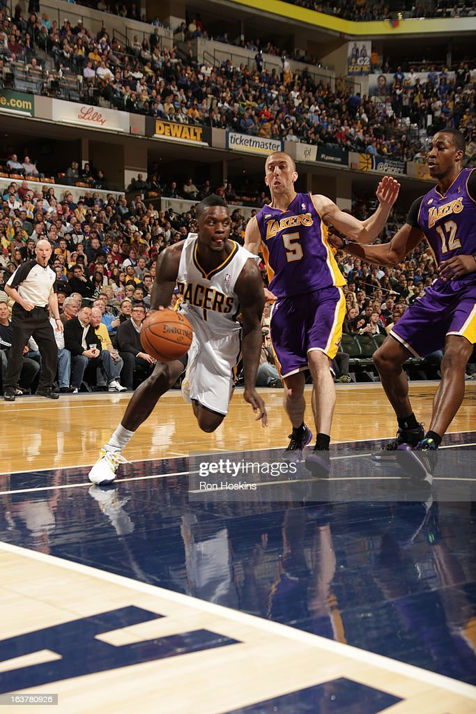 Lance Stephenson #1 of the Indiana Pacers drives against Steve Blake #5 and Dwight Howard #12 of the Los Angeles Lakers on March 15, 2013 at Bankers Life Fieldhouse in Indianapolis, Indiana.