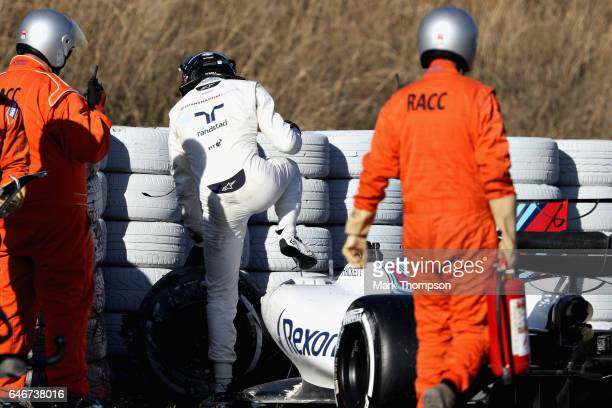Lance Stroll of Canada and Williams climbs out of his car after crashing on track during day three of Formula One winter testing at Circuit de...