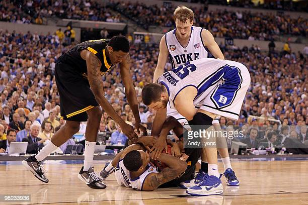 Lance Thomas and Brian Zoubek of the Duke Blue Devils fight for possession of the ball against Kevin Jones and Devin Ebanks of the West Virginia...