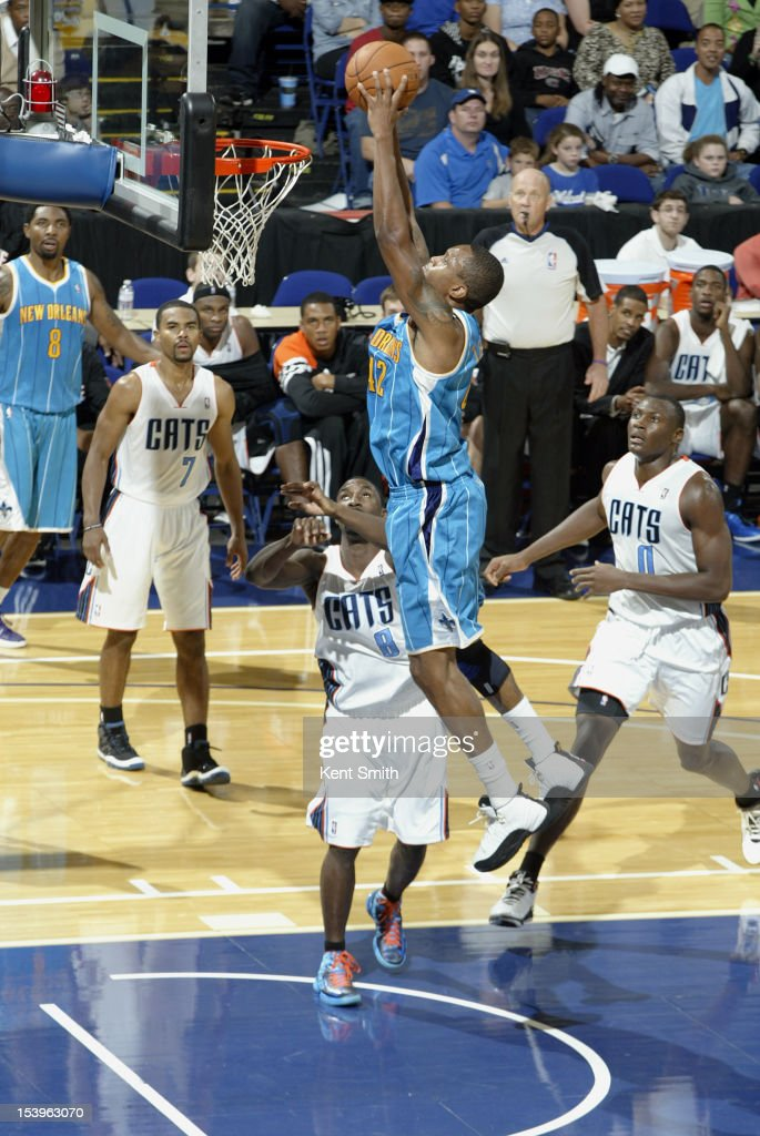 <a gi-track='captionPersonalityLinkClicked' href=/galleries/search?phrase=Lance+Thomas&family=editorial&specificpeople=3847256 ng-click='$event.stopPropagation()'>Lance Thomas</a> #42 of the New Orleans Hornets dunks against <a gi-track='captionPersonalityLinkClicked' href=/galleries/search?phrase=Ben+Gordon&family=editorial&specificpeople=202181 ng-click='$event.stopPropagation()'>Ben Gordon</a> #8 of the Charlotte Bobcats at the North Charleston Coliseum on October 11, 2012 in North Charleston, South Carolina.