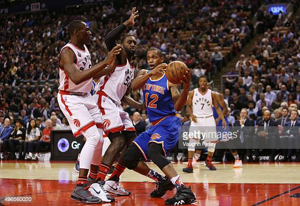 Lance Thomas of the New York Knicks goes up for a shot against Bismarck Biyombo and Patrick Patterson of the Toronto Raptors during an NBA game at...