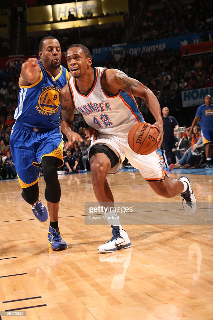 Lance Thomas of the Oklahoma City Thunder drives to the basket against Andre Iguodala of the Golden State Warriors on November 23 2014 at the...
