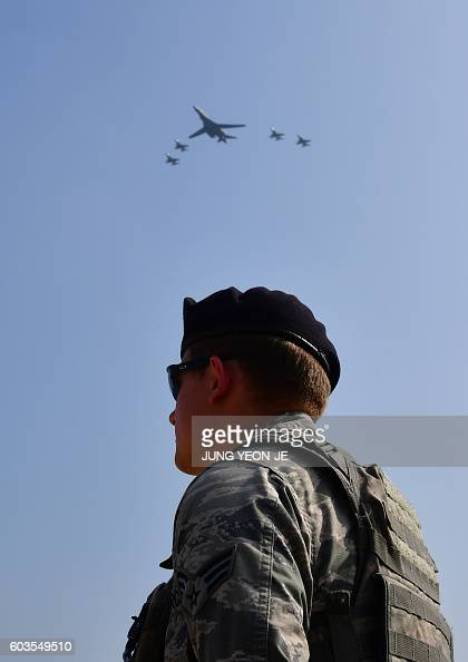 Lancer flies overhead a US soldier standing guard at the Osan Air Base aiming at reinforcing the US commitment to its key ally in Pyeongtaek on...