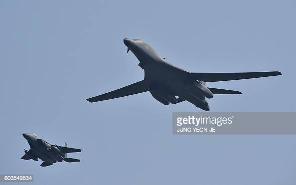 Lancer is escorted by South Korean F15K fighter jets as it flies over the Osan Air Base aiming at reinforcing the US commitment to its key ally in...