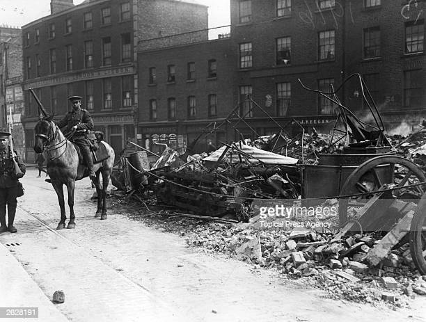 A Lancer on guard in Dublin beside a tramcar used as a barricade during the Easter Rising Fighting occurred after members of the Irish Citizen Army...