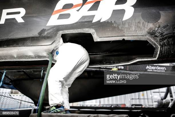 TOPSHOT Land Rover BAR shore team repair the race yacht after a collision with Softbank Team Japan on the second day of the America's Cup on May 28...