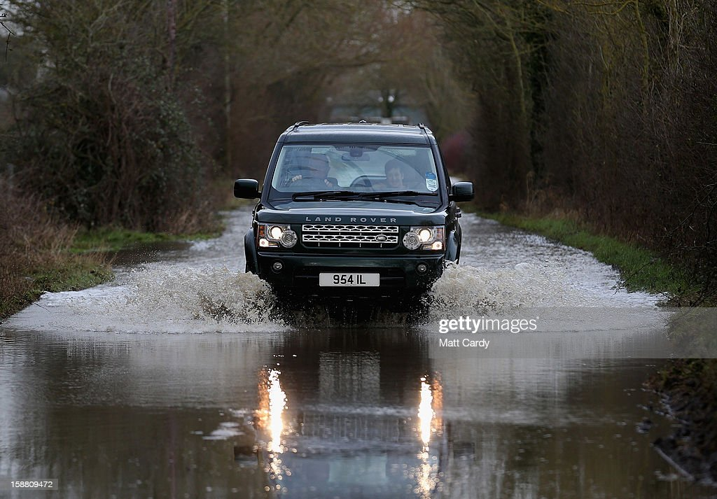 A Land Rover Discovery drives through flood waters surrounding the village of Muchelney, which has been cut off by flooding on the Somerset Levels, on December 30, 2012 near Langport, England. The Met Office is warning of the risk of further flooding towards the end of the year, meaning 2012 is set to be the wettest on record.