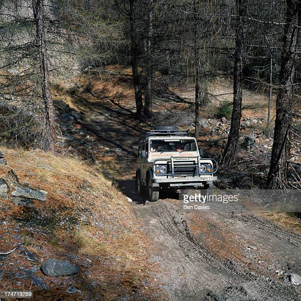 Land Rover filled with tourists from nearby Queenstown drive through magnificent scenery of mountain peaks gorges and the fast flowing waters in...