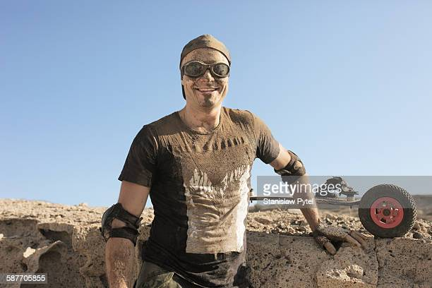 Landboarder covered with mud, smiling