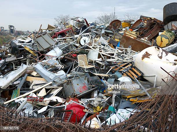 Landfill of metal household items under a gray sky