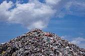 Landfill with blue sky and cumulus clouds, garbage dump in the nature