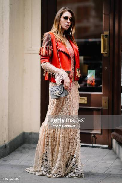 Landiana wears a Nous Mode Clothing red leather jacket with fringes a Furla bag a Marios Karavasilis mesh lace dress outside Topshop during London...