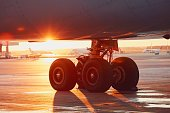 Landing gear of the airplane. Amazing sunset at the airport.