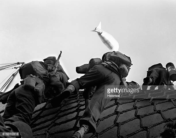 Landing operations at Salerno Italy American soldiers climb down a rope ladder along the side of their transport to Salerno Italy A tethered barrage...