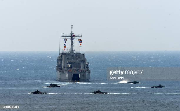 A landing ship is surrounded by the amphibious assault vehicles during the 'Han Kuang' lifefire drill some 7 kms from the city of Magong on the...
