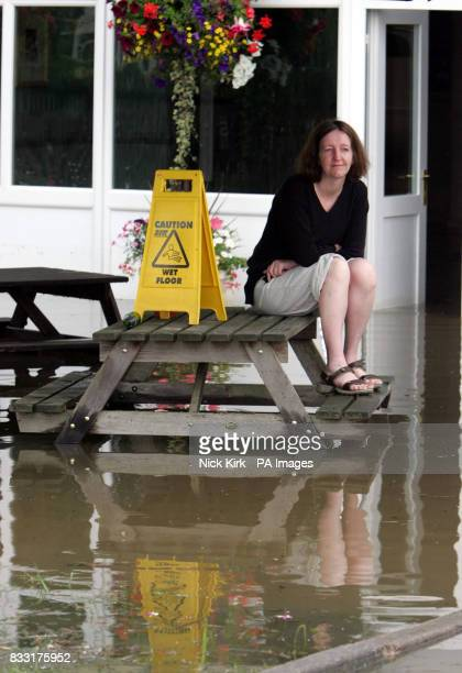 Landlady Amanda Green sits in what used to be her beer garden at The Canterbury in flooded Tewkesbury Gloucestershire