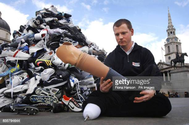 Landmine survivor and BBC journalist Stuart Hughes sits in front of a sculpture of trainers marking Landmine Awareness Day in Trafalgar Square London...