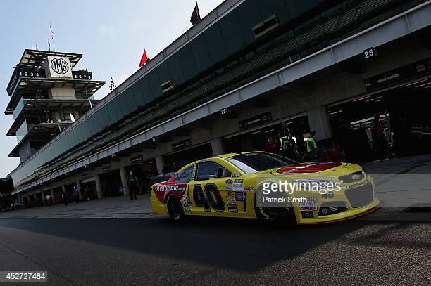 Landon Cassill driver of the Carsforsalecom Chevrolet drives through the garage area during practice for the NASCAR Sprint Cup Series Crown Royal...
