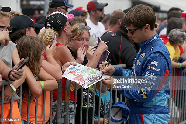 Landon Cassill driver of the Chevrolet signs autographs for fans prior to the NASCAR Sprint Cup Series Crown Royal Presents the Jeff Kyle 400 at the...