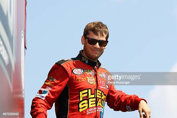 Landon Cassill driver of the Flex Seal Chevrolet takes part in prerace ceremonies for the NASCAR XFINITY Series VFW Sport Clips Help A Hero 200 at...